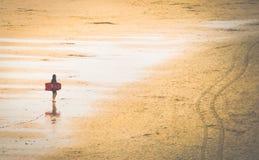 Kobieta na plaży z surfing deską zdjęcie stock