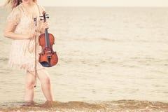 Kobieta na plażowym pobliskim dennym mienie skrzypce Zdjęcia Stock