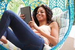 Kobieta Na Plenerowej ogród huśtawce Seat Używać Cyfrowej pastylkę zdjęcia stock