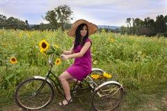 Kobieta na rowerze z słonecznikami Zdjęcia Royalty Free
