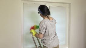Kobieta na schodkach czyści okno zdjęcie wideo