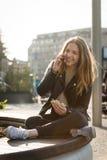 Kobieta na telefonie i łasowanie kanapce Fotografia Royalty Free