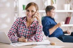 Kobieta na telefonie używać laptop obraz royalty free