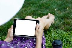 Kobieta na trawie z pastylką Fotografia Royalty Free