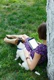 Kobieta na trawie z pastylką Obrazy Stock