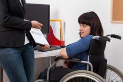 Kobieta na wózku inwalidzkim analizuje mapy z ona szef zdjęcia stock