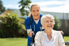 Kobieta na wózku inwalidzkim ma zabawę z pielęgniarką obrazy stock