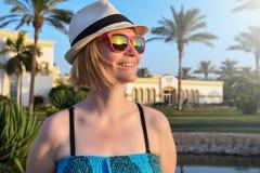 Kobieta na wakacje z różowymi okularami przeciwsłonecznymi i białym kapeluszowym relaksować plenerowymi obraz stock
