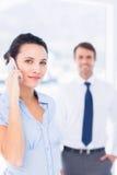 Kobieta na wezwaniu z męskim kolegą w tle Obraz Stock