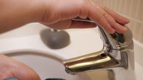 Kobieta naciera faucet z błękitnym płótnem, ręki zbliżenie zbiory
