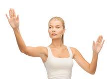 Kobieta naciska imaginacyjnego guzika w białej koszulce Obrazy Stock