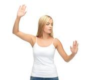 Kobieta naciska imaginacyjnego guzika w białej koszulce Zdjęcie Stock