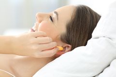 Kobieta nakrywkowi ucho używa prymki na łóżku zdjęcie stock