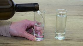 Kobieta nalewa alkohol w strzału szkle z drżącymi rękami zdjęcie wideo