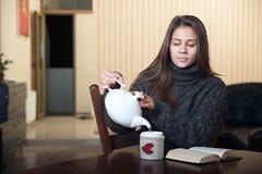 Kobieta nalewa napój w filiżankę Obrazy Royalty Free