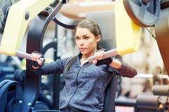 Kobieta napina mięśnie na klatki piersiowej prasy gym maszynie Zdjęcie Stock