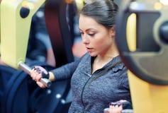Kobieta napina mięśnie na klatki piersiowej prasy gym maszynie Zdjęcia Stock