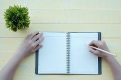 Kobieta napisał książce z glinianą książką w żółtym tle Odgórny widok zdjęcia stock