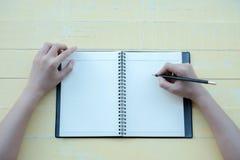 Kobieta napisał książce z glinianą książką w żółtym tle Odgórny widok zdjęcie royalty free