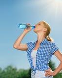 Kobieta napojów woda od butelki w lecie outdoors na s Zdjęcia Stock