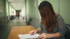Kobieta nauczyciel sprawdza pracy domowej obsiadanie przy biurkiem wewnątrz zbiory