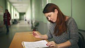 Kobieta nauczyciel sprawdza pracy domowej obsiadanie przy biurkiem wewnątrz zdjęcie wideo