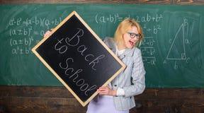 Kobieta nauczyciela formalny kostium trzyma blackboard inskrypcję z powrotem szkoła Dama pedagog w sala lekcyjnej przygotowywa dl obraz stock