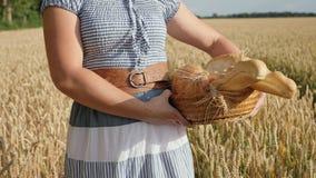Kobieta niesie chleb w koszu na pszenicznym polu zbiory