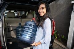 Kobieta niesie galon stawiającego w samochodowym bagażniku woda zdjęcia royalty free