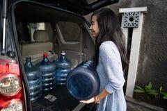 Kobieta niesie galon stawiającego w samochodowym bagażniku woda zdjęcie royalty free