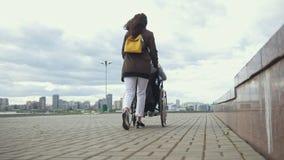 Kobieta niesie niepełnosprawnego mężczyzna w wózka inwalidzkiego odprowadzenia puszku ulica zbiory