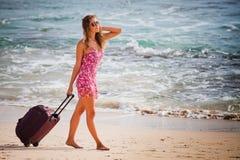 Kobieta niesie twój bagaż przy piaskowatą plażą obraz stock