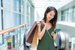 Kobieta niesie z torba na zakupy i używać telefon komórkowy Fotografia Stock