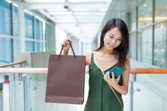 Kobieta niesie z torba na zakupy i używać telefon komórkowy Zdjęcie Royalty Free