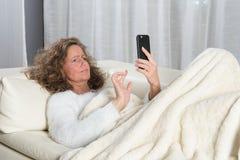 Kobieta no zadawala o wiadomości na smartphone Obraz Royalty Free