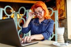 Kobieta obniża jej szkieł spojrzenia przy laptopem przy stołem w cukiernianym zbliżeniu fotografia stock