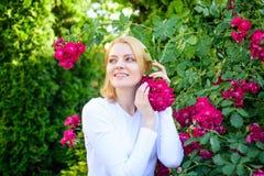Kobieta obwąchuje kwiat woń Czuły perfumowanie i naturalny piękno Dziewczyna i kwiaty na natury tle Wzrastał ekstrakta olej zdjęcia stock
