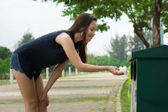 Kobieta ochoczo czyści up ściółkę przy parkiem pomagać chronić nasz środowisko i ochraniać fotografia stock