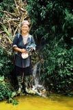 kobieta od czarnej hmong plemienia pozyci obok koloru żółtego barwił strumienia i małą siklawę zdjęcia stock