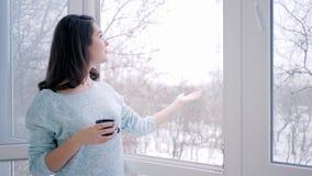 Kobieta oddycha świeże powietrze i pije fragrant herbaty blisko otwartego okno w wakacje zbiory wideo