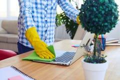 Kobieta odkurza laptop w żółtych rękawiczkach Obrazy Royalty Free