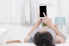 Kobieta odpoczynek i relaksować na łóżku używać telefonów komórkowych przyrząda obrazy royalty free