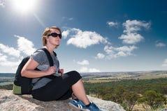 Kobieta odpoczywa na dużej skale zdjęcie stock