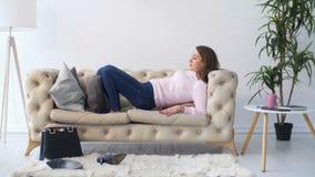 Kobieta odpoczywa na kanapie, z ciekami bierze buty daleko zbiory wideo