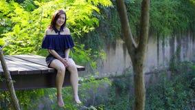 Kobieta odpoczywa na krawędzi drewniany jetty zdjęcie wideo
