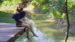 Kobieta odpoczywa na krawędzi drewniany jetty zbiory