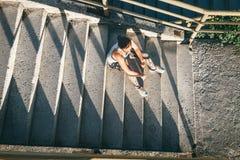 Kobieta odpoczywa na schodkach po tym jak trening ćwiczy Obraz Stock