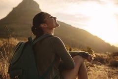 Kobieta odpoczywa po wycieczkować na kraju śladzie zdjęcia stock