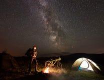 Kobieta odpoczywa przy nocą obozuje blisko ogniska, turystyczny namiot, bicykl pod wieczór niebem gwiazdy pełno obraz stock
