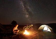 Kobieta odpoczywa przy nocą obozuje blisko ogniska, turystyczny namiot, bicykl pod wieczór niebem gwiazdy pełno obraz royalty free